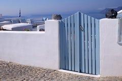 Blue wooden gates in white house, Santorini island, Greece Royalty Free Stock Photo