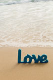Blue Wooden Love word in sand with waves at beach Royalty Free Stock Images