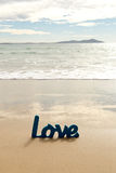 Blue Wooden Love word in sand with waves at beach Stock Photo