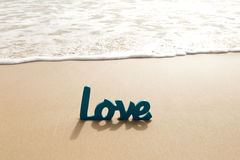 Blue Wooden Love word in sand with waves at beach Royalty Free Stock Image
