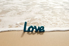Blue Wooden Love word in sand with waves at beach Stock Image