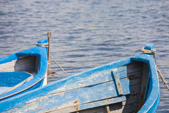 Blue wooden rowing boat on lake. Royalty Free Stock Image