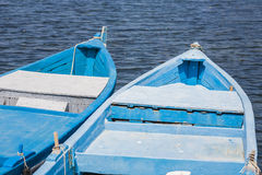 Blue wooden rowing boat on lake. Royalty Free Stock Photo