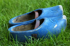 Blue wooden shoes. Old pair of wooden shoes (clogs) in the green grass. Nice contrasting blue and green Stock Images