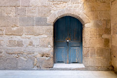 Blue wooden stained aged vaulted ornate door and stone wall Stock Photos