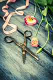 Blue Wooden table with flowers,ribbon and old scissors, florist background Royalty Free Stock Image