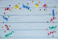 Blue wooden table with free space for text. And colorful ribbons around Stock Photos