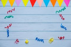 Blue wooden table with free space for text. And colorful ribbons around Stock Image