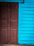 Blue wooden wall and crimson wooden door Royalty Free Stock Photo
