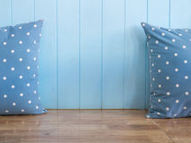 Blue wooden wall with polkadot pillows on wooden bench Royalty Free Stock Photo