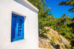 Blue wooden window against clear white wall. Iconic blue wooden window against clear white wall. Typical view for Greek islands, Greece Stock Image