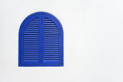 Blue wooden window closed with wooden shutters on white stucco wall Stock Photo