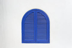 Blue wooden window closed with wooden shutters on white stucco wall Stock Photos