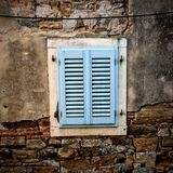 Blue wooden window and an old rustic wall. Old house of brick walls and white window with light blue closed shutters stock photos