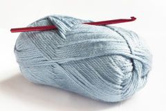 Blue wool and red crochet hook Royalty Free Stock Images