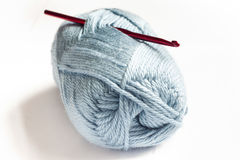 Blue wool and red crochet hook Stock Photos