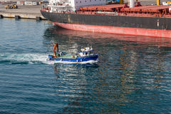 Blue Work Boat Past Tanker royalty free stock image