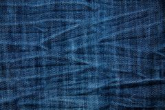 Blue wrinkled denim jeans texture, background Stock Image