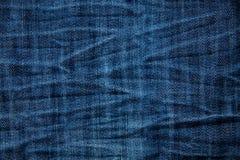 Blue wrinkled denim jeans texture, background. S stock image