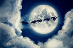 Blue xmas eve night with moon and clouds with Santa Claus sleight and reindeer silhouette flying to bring gifts and Stock Image