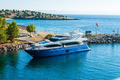 Blue yacht slowly sailing in the bay stock photos