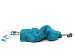 Blue yarn with knitted fabric and knitting needles Royalty Free Stock Photo