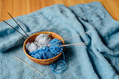Blue yarn in little basket with needles and crochet Royalty Free Stock Image