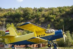 Blue yellow airplane with hungarian flag and landscape background. royalty free stock photography