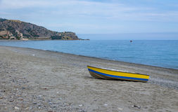 Blue and Yellow boat in a Mediterranean beach of Ionian Sea - Bova Marina, Calabria, Italy Royalty Free Stock Images