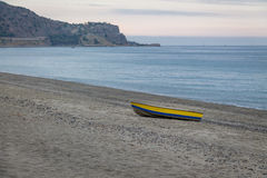 Blue and Yellow boat in a Mediterranean beach of Ionian Sea - Bova Marina, Calabria, Italy Royalty Free Stock Photo