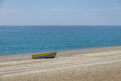 Blue and Yellow boat in a Mediterranean beach of Ionian Sea - Bova Marina, Calabria, Italy Royalty Free Stock Image