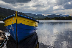 Blue and Yellow boat on still lake. A blue and yellow rowing boat on a still lake with mountains in the background Stock Image