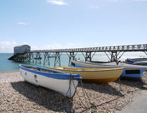 Blue and Yellow Boats on Selsey pebble beach Stock Images