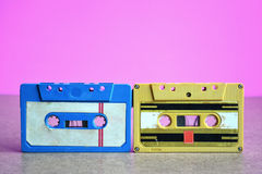 Blue, yellow cassette tapes on pink background. Royalty Free Stock Images