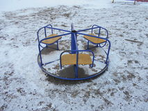 Blue and yellow children's roundabout in the snow park area of ​​the city Stock Photo