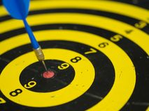 Blue, yellow dartboard and arrows hitting the target stock image