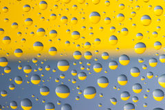 Blue and yellow drops. Blue and yellow water drops on the glass above Ukrainian flag Stock Photo