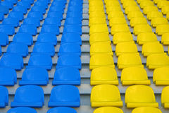 Blue and yellow empty stadium seats. Rows of blue and yellow empty stadium seats Stock Photo
