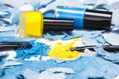 Blue and yellow eyeshadow with nail polishes of the same colors Royalty Free Stock Photo