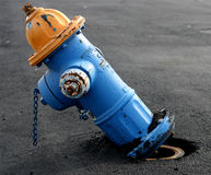Blue and Yellow Fire Hydrant. That Needs Repair Royalty Free Stock Image
