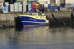 Blue and yellow Fishing boat alongside the wharf. Stock Photo