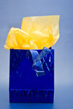 Blue and Yellow Gift Bag. Shiny blue gift back with yellow tissue paper. Against a blue background Stock Photos