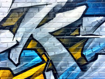Blue and yellow graffiti detail on a brick wall Stock Photos