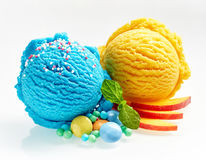 Blue and yellow ice cream. Scoops with candies, mint and apple slices close-up on white background stock image