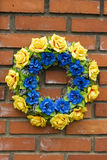 Blue yellow memory wreath. Blue yellow memory wreath on old wall Royalty Free Stock Photos