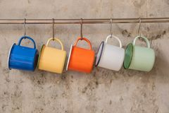 Blue-Yellow-Orange-White-Green tin cup hanging on stainless rail on cement wall background royalty free stock photo