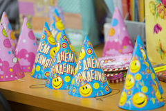 The blue and yellow paper birthday caps on the table Stock Photos
