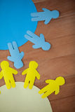 Blue and yellow paper cut-out people on the circle. Conceptual image of blue and yellow paper cut-out people on the circle Royalty Free Stock Photo