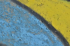 Blue and yellow peeling paint. Rough concrete wall with weathered peeling blue and yellow paint Stock Photos