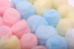 Blue, yellow and pink hygienic cotton balls in row. S isolated on a white background royalty free stock photography